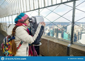 Woman looking through viewer on top of New York's Empire State building
